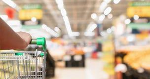 Vagn för shopping för supermarket för kvinnahandhåll med suddig bakgrund för livsmedelsbutik arkivfoto
