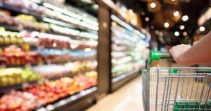 Vagn för shopping för supermarket för kvinnahandhåll med suddig defocused bakgrund för abstrakt livsmedelsbutik royaltyfri foto