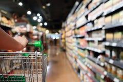 Vagn f?r shopping f?r kvinnahandh?ll med suddighetssupermarketbakgrund fotografering för bildbyråer