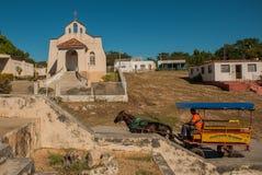 Vagn med hästen och mannen Liten katolsk kyrka i en by nära staden Cienfuegos, Kuba royaltyfri bild