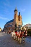 Vagnar för att rida turister på bakgrunden av den Mariacki domkyrkan Arkivbild