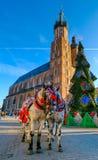 Vagnar för att rida turister på bakgrunden av den Mariacki domkyrkan Arkivfoto
