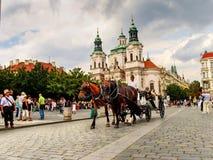 Vagnen med hästar och St Nicholas kyrktar i den gamla stadfyrkanten i Prague, Tjeckien royaltyfria bilder