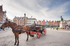 Vagnen på den Grote Markt och Belfort skåpbilen Brugge Royaltyfria Bilder
