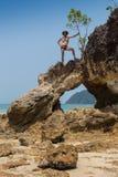 Vago masculino atractivo de la playa del vagabundo que toma en una roca Fotografía de archivo libre de regalías