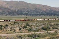 Vagoni coperti variopinti su un treno merci sull'alto deserto Fotografia Stock