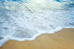 Vague avec la mousse sur une plage tropicale photos stock