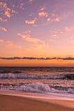 Vague déferlante d'océan sous les nuages d'or Photos stock