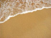 Vague déferlante de l'eau de plage de sable Image stock