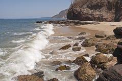 Vague déferlante, rochers et plage photo stock
