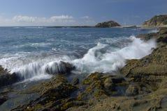 Vague déferlante se cassant sur le regroupement côtier rocheux de marée photo libre de droits
