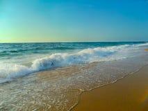 Vague de mer blanche de neige s'opposant dedans à la plage Image stock