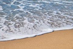 Vague de mer sur le sable d'or chaud Photos stock