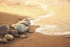 Vague de mer sur le sable et pierre au lever de soleil Photos libres de droits