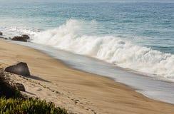 Vague de rupture avec backspray sur une plage sablonneuse avec des rochers et iceplant, avec un horizon d'?tendue d'oc?an photographie stock