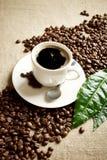 Vague diagonalement faite de grains de café avec la tasse de café écumeux avec la feuille Photographie stock