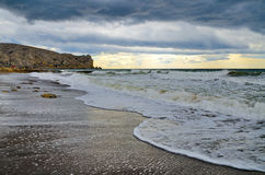 Vague du ressac sur une plage sablonneuse par temps nuageux La Crimée, Sudak Photographie stock libre de droits