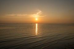 vague et plage de coucher du soleil Images stock