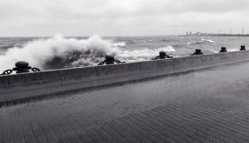 Vague forte se brisant contre le pilier au bord de mer dans le weathe orageux photographie stock
