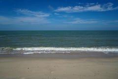 Vague molle de mer de mousse sur la plage sablonneuse blanche avec le ciel bleu et le fond blanc de nuage Images stock