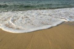Vague molle mousseuse sur la plage de sable Photos stock