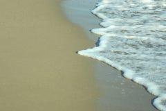 Vague mousseuse de mer de plage au-dessus du sable Photo stock