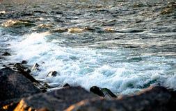 Vague moyenne basculant contre des roches photo libre de droits