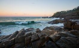 Vague se brisant au-dessus des roches Photographie stock
