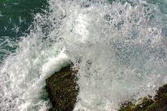 Vague se brisant contre des roches sur la plage Image libre de droits