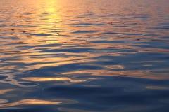 Vague sur la surface de mer au coucher du soleil image stock