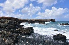Vagues éclaboussant dessus pour noircir Lava Rocks sur la plage d'Aruba Images libres de droits