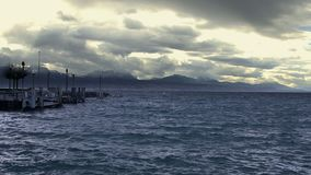 Vagues éclaboussant sur la surface variable de l'eau, cloudscape orageux, montagnes sur l'horizon banque de vidéos