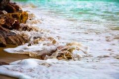 Vagues blanches et mer bleue sur la plage brune de sable image stock