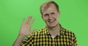 Vagues caucasiennes belles d'homme et salutation sur la clé verte de chroma d'écran banque de vidéos