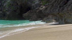 Vagues clair comme de l'eau de roche de mer éclaboussant sur le rivage arénacé sur le fond de falaise L'eau d'océan de turquoise  banque de vidéos
