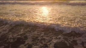 Vagues d'eau de mer sur la plage sablonneuse tandis que lever de soleil d'or au matin d'été Coucher du soleil de vue de bourdon b banque de vidéos