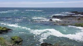 Vagues dans l'océan à une plage rocheuse banque de vidéos