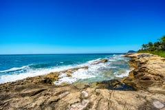 Vagues de l'océan pacifique se brisant sur le rivage rocheux de la côte ouest de l'île d'Oahu images libres de droits