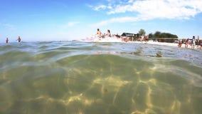 Vagues de mer, ciel bleu et touristes de natation banque de vidéos