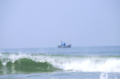 Vagues de mer et bateau du pêcheur Images stock