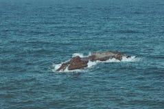 Vagues de mer frappant la pierre Photographie stock libre de droits