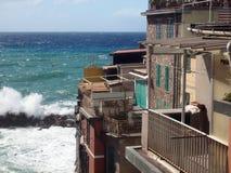 Vagues de Riomaggiore Cinque Terre Italy se cassant contre h historique Image stock