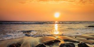 Vagues et roches sur la plage du coucher du soleil Image stock