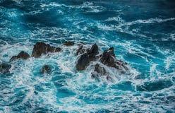 Vagues faisantes rage bleues se brisant sur les roches Photos stock