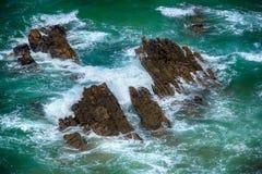 Vagues faisantes rage bleues se brisant sur les roches Image stock