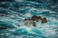 Vagues faisantes rage bleues se brisant sur les roches Photographie stock