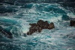 Vagues faisantes rage bleues se brisant sur les roches Images stock