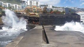 Vagues frappant le pont et les roches de Funchal, Madère image stock