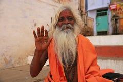 Vagues habillées orange d'ascétique tout en se reposant à Varanasi, Inde photographie stock libre de droits