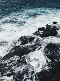 Vagues mousseuses au rivage d'océan au coucher du soleil image libre de droits
